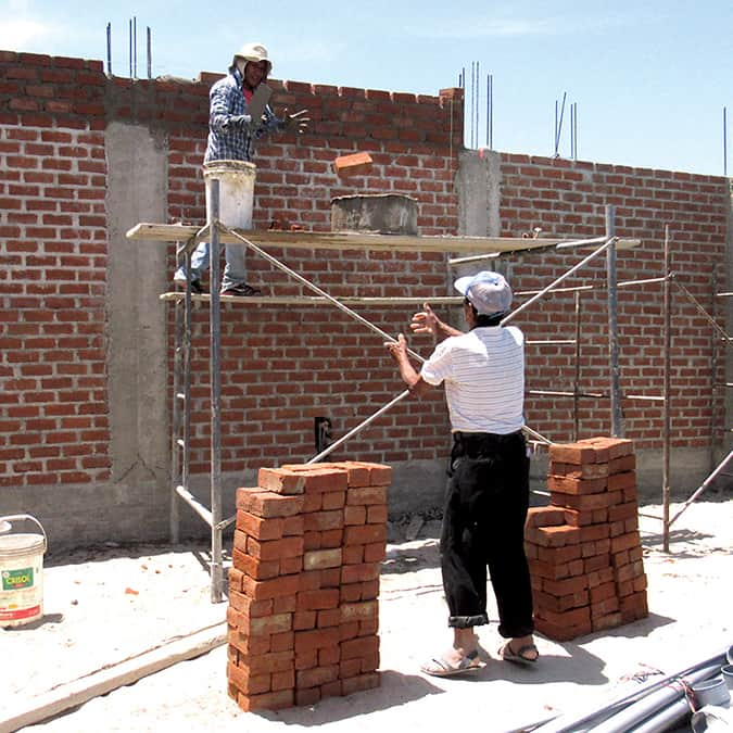 Workers building the brick wall